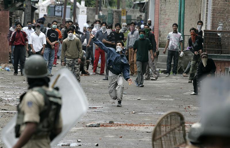 Kashmiri protesters throw stones and bricks towards Indian policemen during a protest in Srinagar
